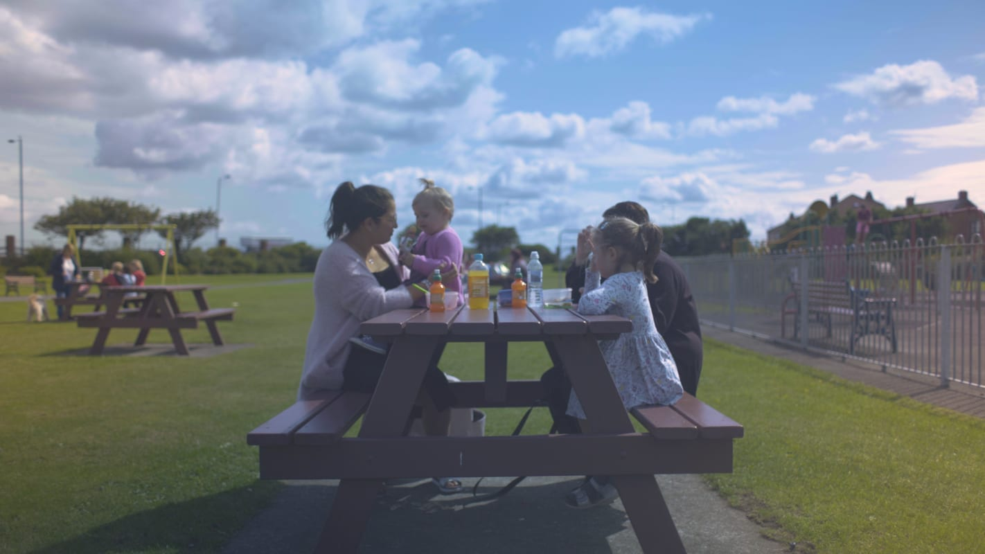 Photograph of a family having at a picnic bench in Zetland Park